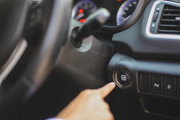 Bouton d'arrêt de démarrage à la main sur le tableau de bord de la voiture