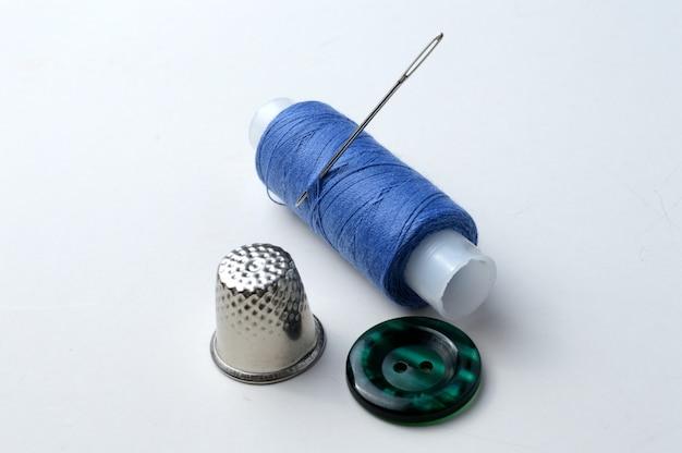 Bouton, une bobine de fil avec une aiguille, un dé et un bouton sur fond clair