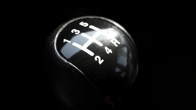 Bouton de boîte de vitesses à cinq vitesses sur noir, mise au point sélective.