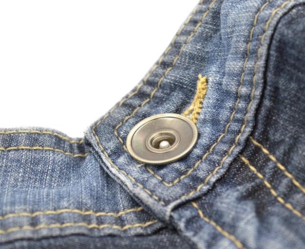 Bouton en métal sur jean bleu sur ceinture près d'une fermeture.