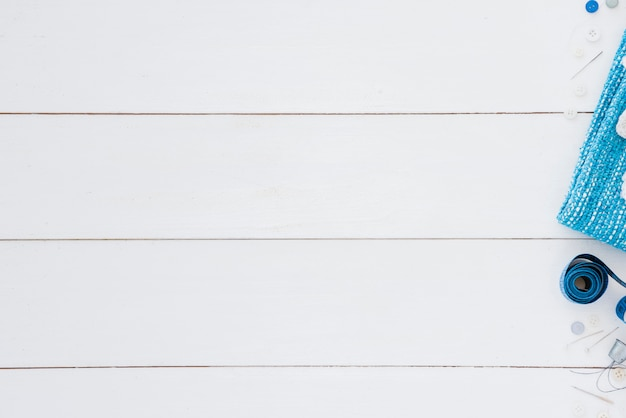 Bouton; mètre ruban; aiguille et dé à coudre sur le bureau blanc avec espace pour l'écriture du texte