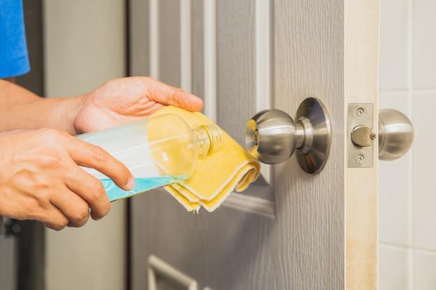 Bouton de porte de nettoyage à la main avec de l'alcool et un chiffon en microfibre jaune.