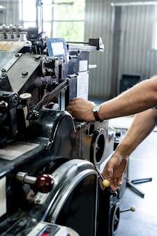 Bouton de presse de doigt de main d'ingénieur contrôlant la machine de commande numérique par ordinateur, entrepôt de machines d'usine d'exploitation