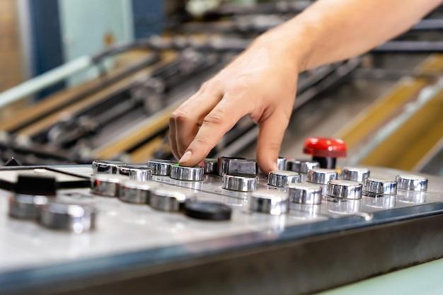 Bouton de presse de doigt de main d'ingénieur contrôlant la machine de commande numérique par ordinateur, ouvriers fonctionnant l'entrepôt d'usine