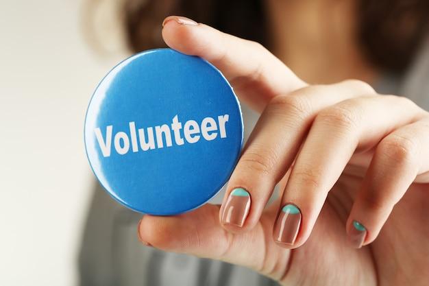 Bouton rond volontaire en gros plan de main