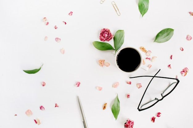 Bouton de rose rouge, verres, feuilles, café sur une surface blanche