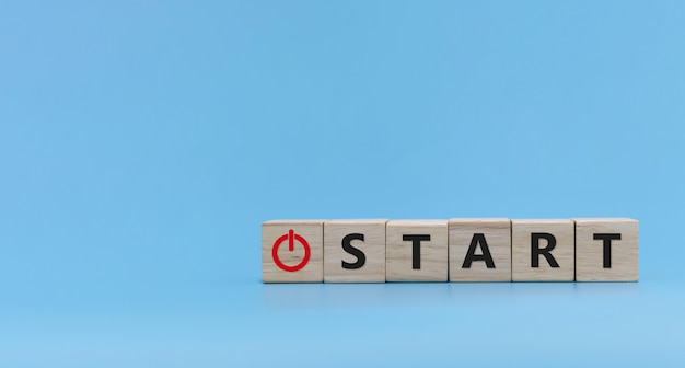 Bouton start. mot start écrit sur une pile de blocs de cubes en bois sur fond bleu, félicitations pour le nouvel an, idée, finance, stratégie, démarrage d'entreprise, marketing en ligne, concept d'objectif et de plan cible