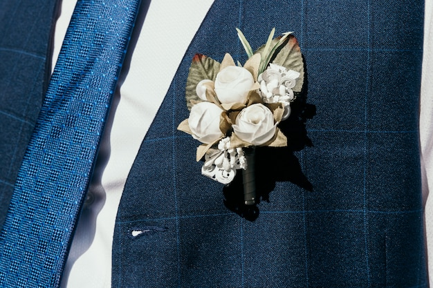 Une boutonnière artificielle percée dans le gilet du marié.