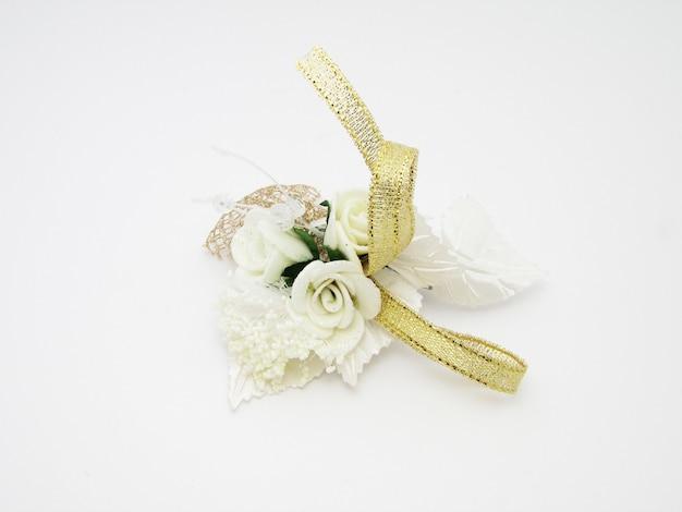 Boutonnière avec fleurs blanches et ruban d'argent isolé sur fond blanc