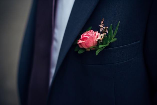 Boutonnière de fleurs fraîches sur le costume du marié