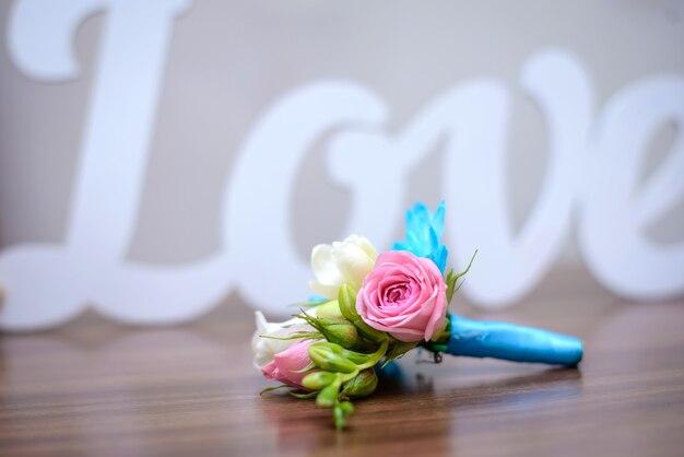 Boutonnière de mariage de fleurs roses et bleues pour le marié sur une table en bois dans le contexte du mot amour