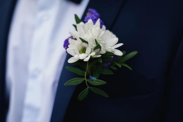 Boutonnière de mariage de marguerites blanches sur la veste bleue du marié