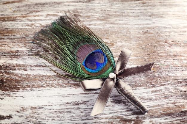 Boutonnière de mariage avec plume de paon sur fond de bois