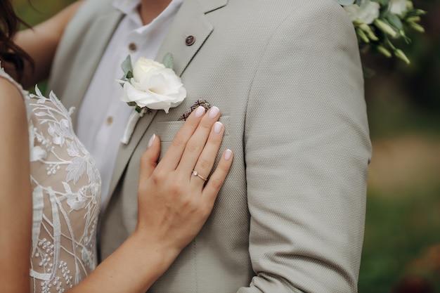Boutonnière avec une rose sur le fond de la veste du marié.