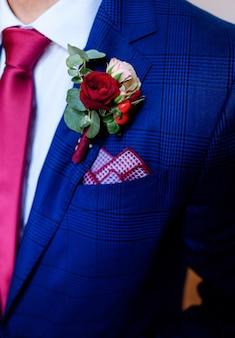 Boutonnière rouge foncé épinglée à la veste bleue du marié