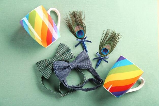Boutonnières de mariage avec plume de paon, tasses colorées et nœuds papillon sur fond turquoise