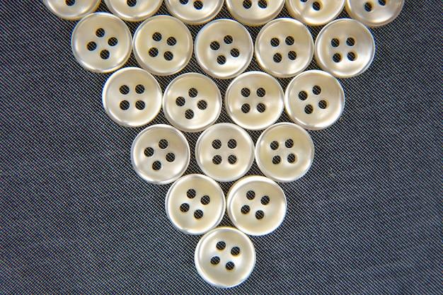 Boutons brillants en plastique pour vêtements sur fond de tissu. mode et habillement. industrie d'usine