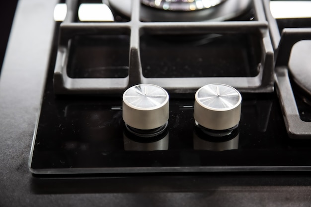 Boutons de brûleur de cuisinière à gaz avec surface miroir noire de la cuisinière et grilles en acier inoxydable vue de dessus fermer