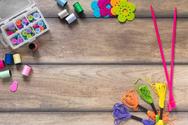 Boutons colorés dans une boîte avec une bobine; aiguilles tricotées et fil de soie sur table en bois