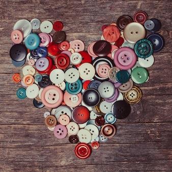 Boutons colorés en forme de coeur sur la table en bois vintage