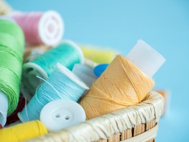 Boutons de couture colorés et fil dans une boîte en bois sur fond bleu