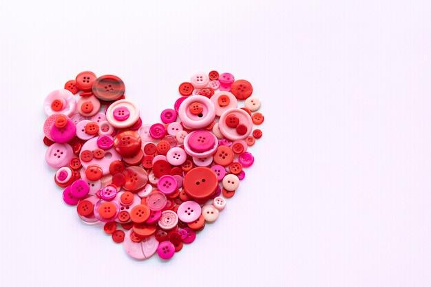 Boutons de couture rouges en forme de coeur sur fond blanc