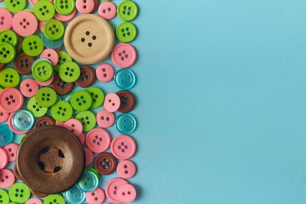 Boutons de couture en tas sur la surface cyan. mise à plat avec espace copie