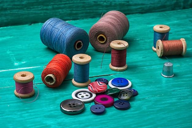 Boutons de fil pour l'artisanat sur fond en bois turquoise.