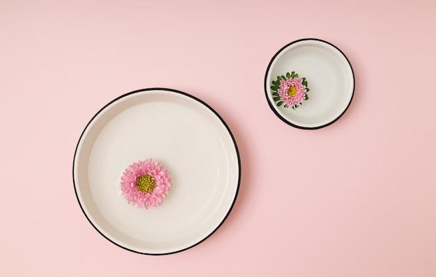 Boutons de fleurs de chrysanthème rose flottant dans de grands et petits bols ronds blancs avec de l'eau sur fond rose. mise à plat naturelle minimale.