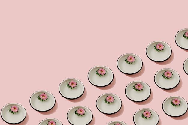 Boutons de fleurs de chrysanthème rose flottant dans de petits bols ronds avec de l'eau sur fond rose. mise à plat naturelle minimale. modèle sans couture.