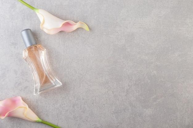 Boutons de fleurs roses artificielles avec bouteille de parfum sur pierre.