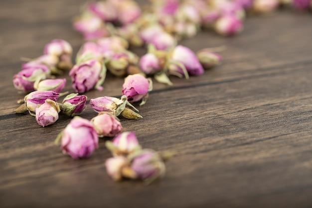 Boutons de fleurs de roses séchées placés sur une table en bois