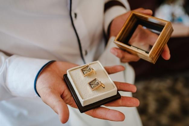 Boutons de manchette du marié dans une boîte, boutons de manchette masculins en or.