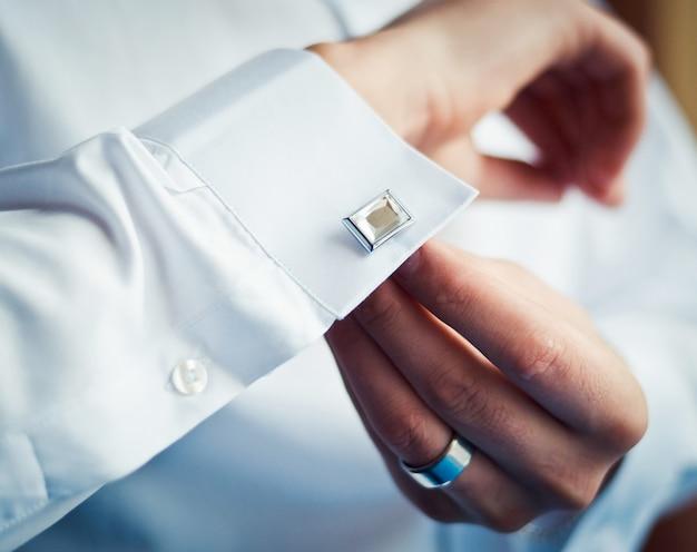 Boutons de marié sur ses poignets de chemise
