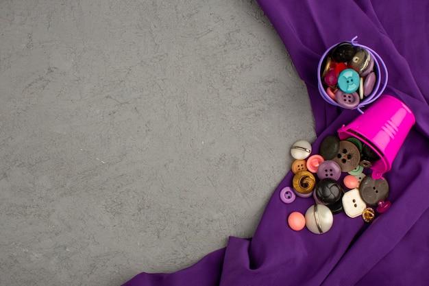 Boutons en plastique coloré vintage à l'intérieur de pots violets et roses sur un tissu violet et un bureau gris