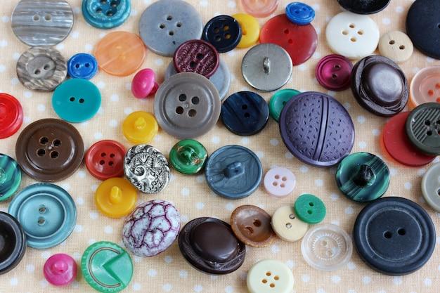Boutons en plastique multicolores éparpillés sur la table