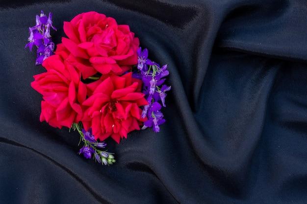 Boutons de rose avec des fleurs bleues sur fond noir arrangement floral place à plat pour l'espace de copie de texte