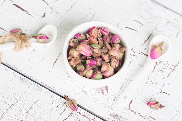 Boutons de rose séchées sur un fond en bois blanc