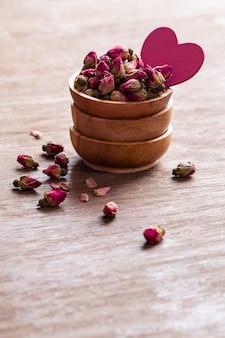 Boutons de rose séchés rose rouge dans un bol en bois
