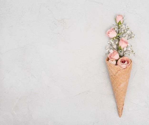 Boutons de roses en cornet de crème glacée et espace copie