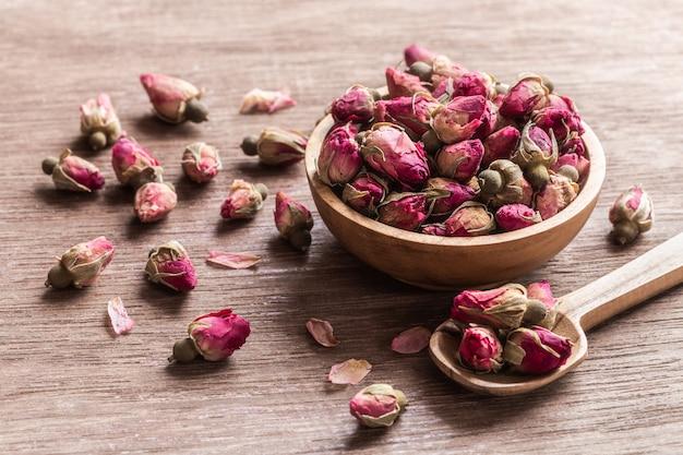 Boutons de roses séchées rouges roses dans un bol en bois avec des pétales sur fond en bois ancien.