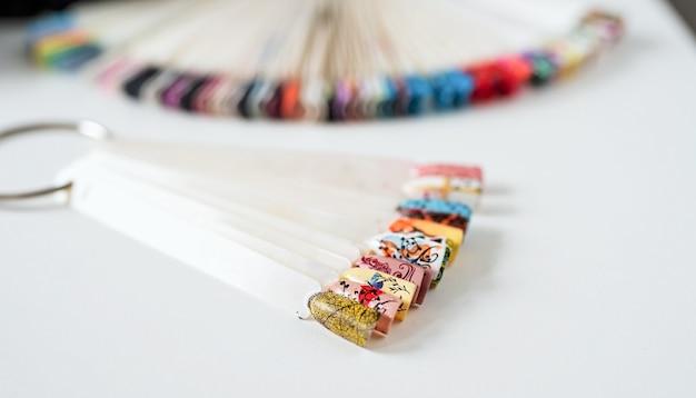 Bouts d'ongles en plastique colorés avec divers modèles d'ongles sur la table dans un salon de manucure