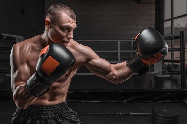 Boxe de combattant musculaire contre le ring. concept d'arts martiaux mixtes.