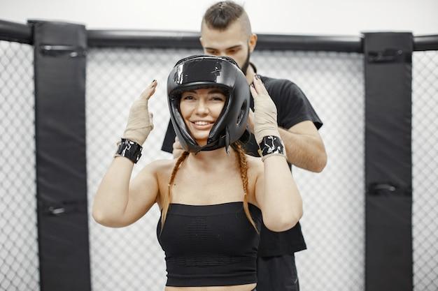 Boxe femme. débutant dans une salle de sport. dame dans un vêtement de sport noir. femme avec entraîneur.