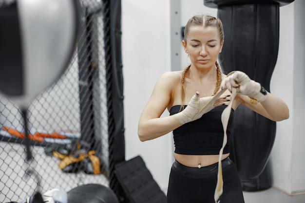 Boxe femme. débutant dans une salle de sport. dame dans un vêtement de sport noir.