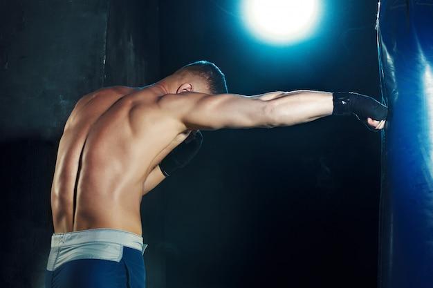 Boxe homme boxe dans un sac de boxe