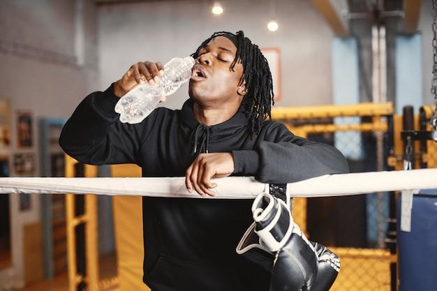 Boxe homme sportif. photo de boxeur sur un ring. homme afro-américain avec une bouteille d'eau.