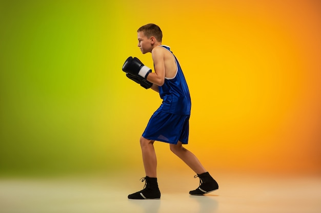 Boxer adolescent sur fond de studio néon dégradé en mouvement de coups de pied, boxe