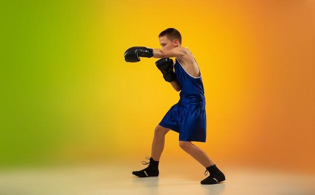 Boxer adolescent sur fond de studio néon dégradé en mouvement de kick boxing