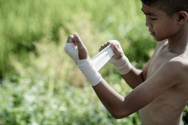 Boxer asiatique petit garçon avec nature